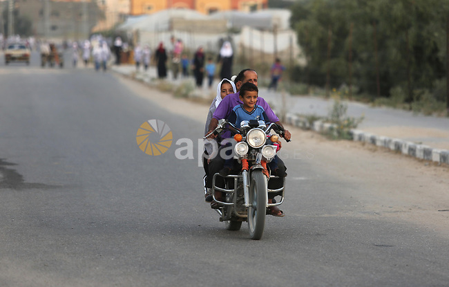 Palestinian schoolchildren ride motorcycle as they make their way to school on the first day of a new school year, at a United Nations-run school in Deir al-Balah refugee camp in the central Gaza Strip August 23, 2017. Photo by Ashraf Amra