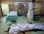 A woman's body lies in the emergency ward at Mirwais Hospital in Kandahar, Afghanistan, Saturday morning, Apr. 18, 2009. Two people were killed and five more were injured when a bomb detonated just outside the hospital, as a police vehicle went by. Afghan police said the explosion was set off by a suicide bomber. Doctors said this woman was already dead when she arrived at the hospital. Despite worsening security, development continues at Mirwais Hosptial, where the International Committe of the Red Cross conducts training and assists the local staff. Mirwais is the main public hosptial serving five southern provinces. As security has deteriorated in the South, many international NGO's have pulled their staff from the area or shut down the regional office, stunting development in a region where it is badly needed.