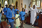 As a woman dances in the aisle, a children's choir sings during a worship service of Nuer refugees from South Sudan who live in Cairo, Egypt. The service took place at St Andrews United Church of Cairo.