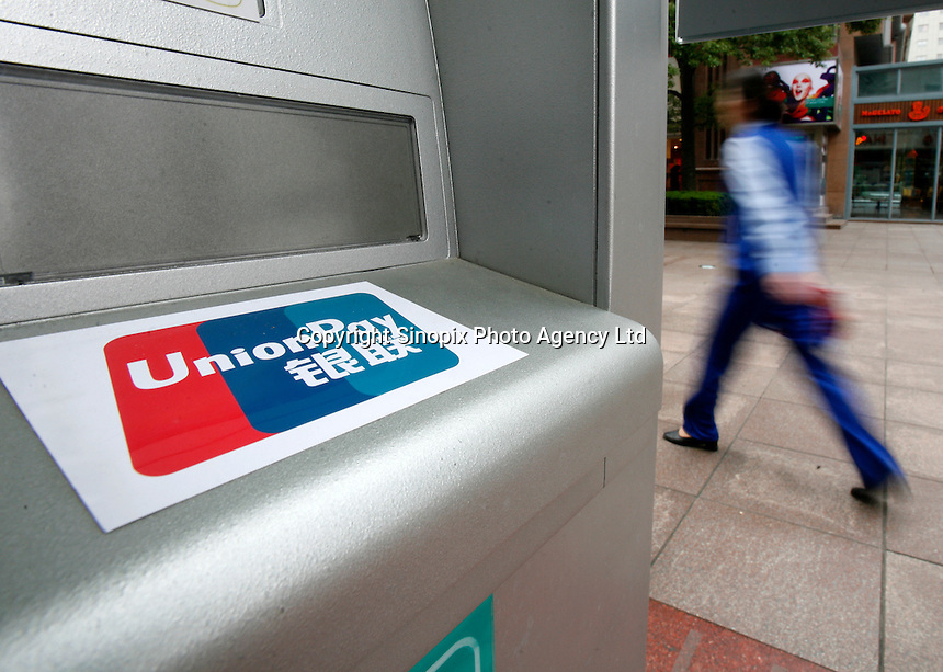 A pedestr.ian walks past a bank ATM machine with an UnionPay sticker in Shanghai, China. There are all together more than 86,000 ATM machines with Union Pay logo in China..