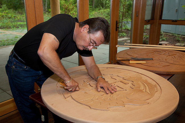 Coast Salish wood carver demonstrates  his craftsmanship while carving a large traditional cedar wood disk at the Hilbub Cultural Center and Museum located on the Tulalip Tribes Reservation in Marysville, WA