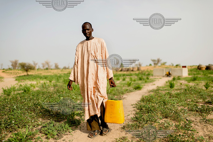 A man carrying a bucket of water, an unususal sight as this is usually done by women and children, in the village of Din-Rimi.