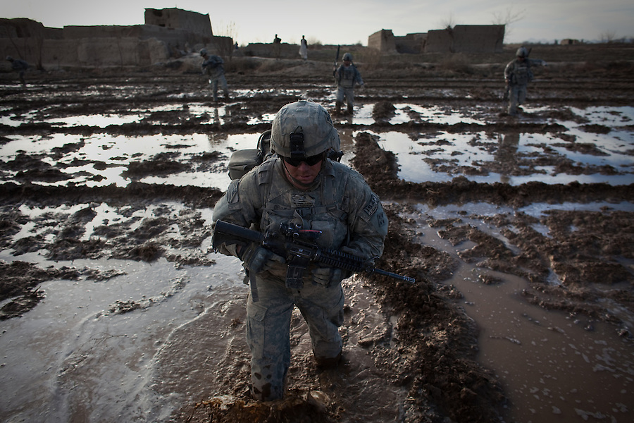 A trooper with Charlie Co. 1st Battalion 12th Infantry Regiment, 4th Infantry Division slogs his way through a flooded field during a patrol in Zhari District, Kandahar, Afghanistan. The violently contested district sits astride the strategically Highway 1 ringroad between Kandahar and Lashkar Gah and is seen by some as the birthplace of the Taliban movement.=