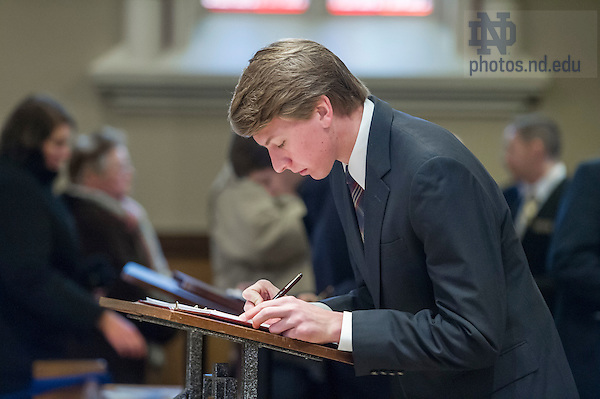 Mar. 4, 2015; A student signs the Guest Book during the visitation of President Emeritus Rev. Theodore M. Hesburgh, C.S.C., in the Basilica of the Sacred Heart. (Photo by Barbara Johnston/University of Notre Dame)