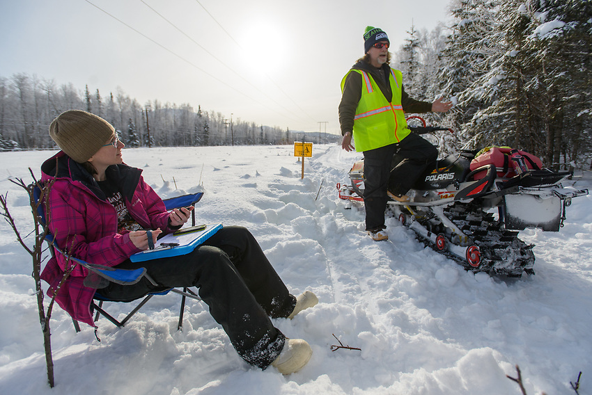 Fur Rondy Open World Championship Sled Dog Race volunteers Aleria Knudson and Steve Cole monitor a checkpoint in Anchorage's Bicentenial Park.