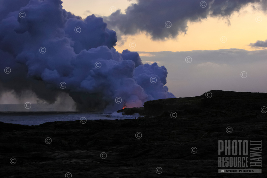 Large cloud of smoke rises as lava meets the ocean along the coastline on the Big Island.