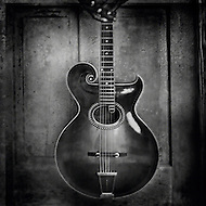 A man holds a beautiful acoustic guitar in front of an old door