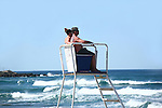 Young couple looking out at ocean in life-guard chair