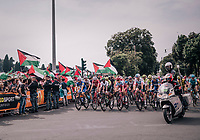 peloton cruising in Rome in front of Palestinian protesters<br /> <br /> stage 21: Roma - Roma (115km)<br /> 101th Giro d'Italia 2018