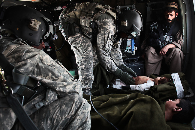 "As a male relative looks on, Staff Sgt. Rakheem Francis, 24, of Queens, N.Y., a flight medic with the 101st Combat Aviation Brigade's ""Shadow Dustoff""  treat two Afghan children who were injured in a bomb explosion in the Arghandab valley near Kandahar, Afghanistan. The two children survived their injuries. Sept. 19, 2010. DREW BROWN/STARS AND STRIPES"