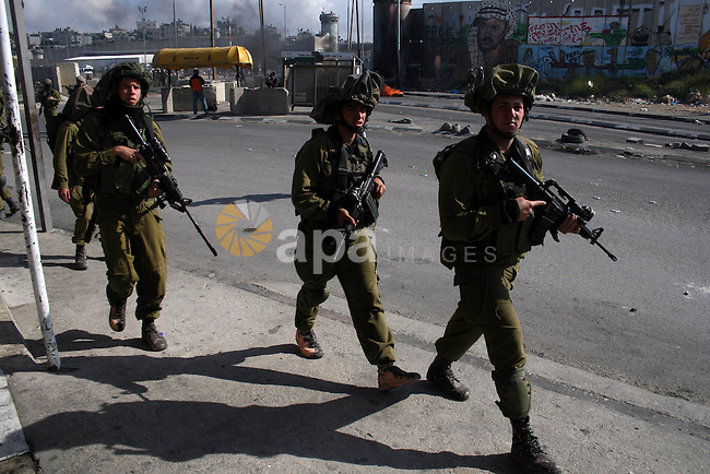 """Israeli soldiers run past burning tires during clashes with Palestinian stone throwers at the Israeli manned Qalandia checkpoint between Jerusalem and the West Bank city if Ramallah on May 14, 2011, as Palestinians gather in the run up to tomorrow's 63rd anniversary of the 1948 creation of Israel, an event known to Arabs as the """"nakba"""" or """"catastrophe. Photo by Issam Rimawi"""