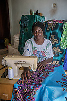 Uganda, Bujuuko. Jalia Musoke runs a tree farm and sewing business. She is busy with work and chores and uses a BioLite wood cook stove that she feels is faster than a regular cookstove. Here she in her home based sewing busnisee.