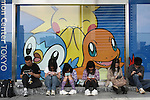 """May 9, 2010 - Tokyo, Japan - Young and adults Japanese people play Nintendo's portable video game 'DS' in front of the official Pokemon store in Tokyo on May 9, 2010. Nintendo recently announced that the DS handheld device had become the best selling gaming handheld of all time, with a total of 129 million units sold. The DS 'family' have surpassed the """"Game Boy"""" series which hit 118 million over two decades."""