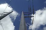 Clouds seem to race past the tops of transmission line poles.