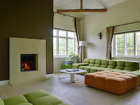 A green and orange modular sofa and ottoman are grouped around a contemporary fireplace in the living room