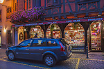 Car and man in front of a food store in Ribeauville, France,
