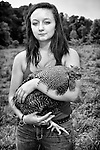 A young farm girl holding a rooster at Kirby Family Farm in Middletown, New York