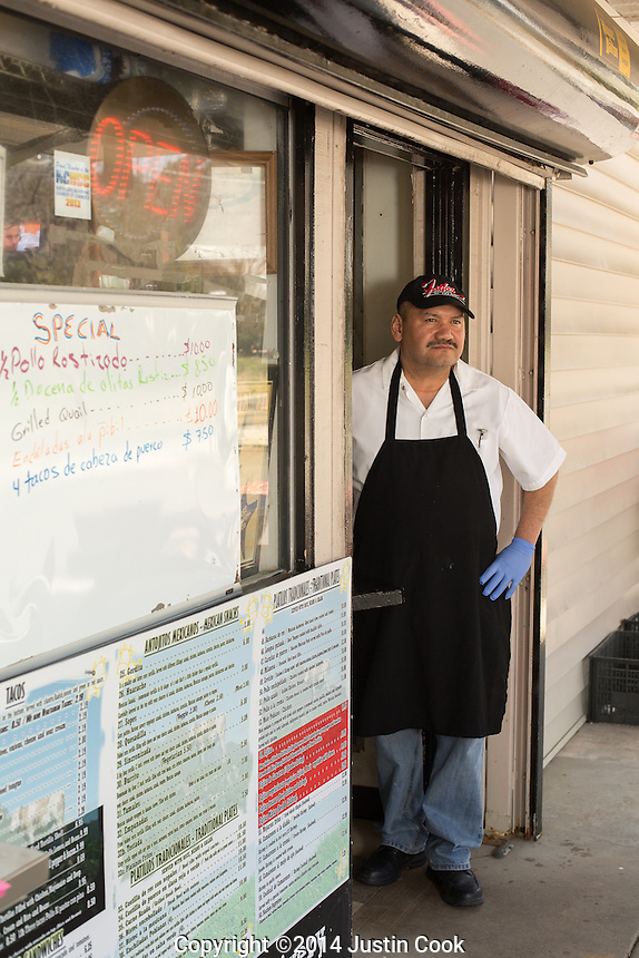 Fidel Rodriguez of La Vaquita Taqueria and some yummy enchildas in Durham, N.C. on Thursday, March 27, 2014. (Justin Cook)