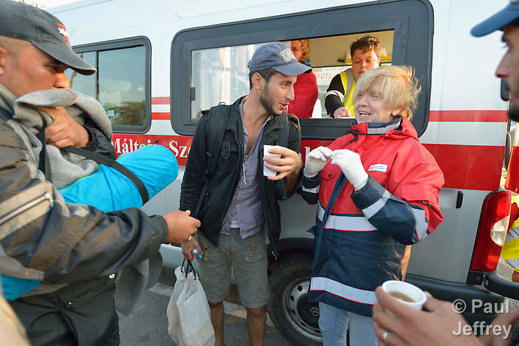 Hungarian volunteers with Malteser International, a Catholic organization, share conversation as they give coffee to migrants and refugees passing through the Hungarian town of Hegyeshalom and prepare to cross the border into Austria. Hundreds of thousands of refugees and migrants flowed through Hungary in 2015, on their way to western Europe from Syria, Iraq and other countries. Malteser International is the relief agency of the Sovereign Order of Malta.