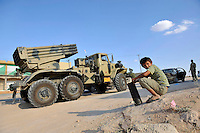 A boy plays with an empty cartridge of ammunition next to a rebel vehicle with a multiple rocket launcher. After a six month revolution, rebel forces finally managed to break into Tripoli and have taken control of Bab al-Aziziyah, Col Gaddafi's compound and residence. Few remain that are loyal to Gaddafi in the city; it is seeming that the 42 year regime has come to an end. Gaddafi is currently on the run.