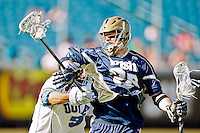 February 20, 2011:   Notre Dame midfield Zach Brenneman (28) fights off the stick from Duke long stick midfielder CJ Costabile (9) during Lacrosse action between the Duke Blue Devils and Notre Dame Fighting Irish during the Moe's Southwest SunShine Classic played at EverBank Field in Jacksonville, Florida. Notre Dame defeated Duke 12-7.