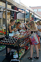 Young woman shopping at a fruit vendor's stall in the Jean Talon public market or Marche Jean Talon, Montreal, Quebec, Canada