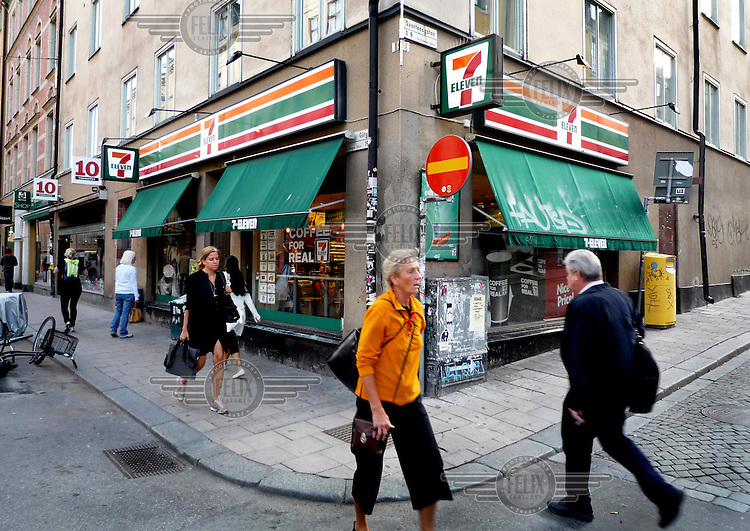 Pedestrians pass a 7-Eleven convenience store that Lisbeth Salander, a character created by author Stieg Larsson, frequents in his Millennium trilogy novels.