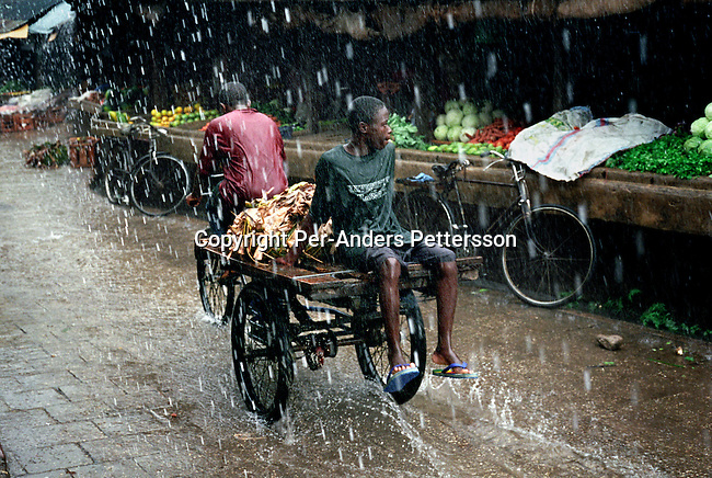 A man sitting on a bicycle fruit cart at a vegetable market during a heavy rainfall on October 8, 2002 in Stone Town in central Zanzibar, Tanzania. Zanzibar has become a popular tourist destination due to the beautiful virgin beaches and influence of Arabic, Indian and African cultures on the Island. The Island is mostly Muslim and was a center for slave trade, and its estimated that around 600,000 slaves were sold on Zanzibar between 1830 and 1873. (Photo by: Per-Anders Pettersson)