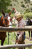 USA, Wyoming, Encampment, a wrangler puts a bridle on a horse before a trail ride, Abara Ranch