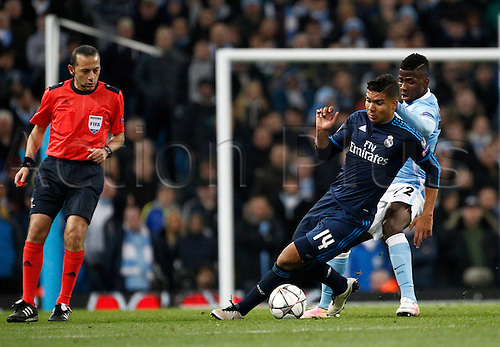 26.04.2016. The Etihad, Manchester, England. UEFA Champions League. Manchester City versus Real Madrid. Referee Cuneyt Cakir looks on asReal Madrid midfielder Casemiro turns past Manchester City striker Kelechi Iheanacho