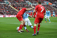 Raheem Sterling of Manchester City (centre) is tackled by Jordan Henderson of Liverpool (left) as James Milner of Liverpool (right) looks on during the Capital One Cup match between Liverpool and Manchester City at Wembley Stadium, London, England on 28 February 2016. Photo by David Horn / PRiME Media Images.