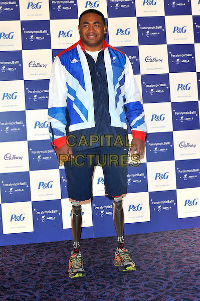 Derek Derenalagi.The Paralympic Ball in aid of the British Paralympic Association & the Agitos Foundation, Grosvenor House Hotel, Park Lane, London, England..September 5th, 2012.full length black white red blue tracksuit shorts legs amputee amputated prosthetics .CAP/CJ.©Chris Joseph/Capital Pictures.