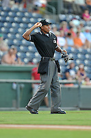 Umpire Edwin Moscoso works the plate in a game between the Greensboro Grasshoppers and the Greenville Drive on Thursday, August 27, 2015, at Fluor Field at the West End in Greenville, South Carolina. Greenville won, 10-2. (Tom Priddy/Four Seam Images)