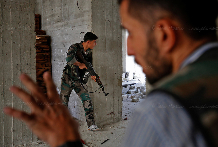 Free Syria Army soldiers exchange small arms fire with loyalist troops in the Saif-Al-Dawla district of Aleppo.