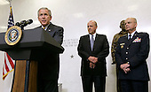 Langley, VA - May 31, 2006 -- United States President George W. Bush, left, speaks during a ceremonial swearing in for new Central Intelligence Agency Director General Michael Hayden right, as National Intelligence Director John Negroponte, center, looks on, at CIA headquarters in Langley, Virginia Wednesday 31 May 2006. Hayden, the former head of the super-secret National Security Agency (NSA), was officially sworn-in yesterday in a closed ceremony.<br /> Credit: Matthew Cavanaugh-Pool via CNP
