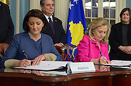 December 14, 2011  (Washington, DC)  U.S. Secretary of State Hillary Clinton and the President of Kosovo, Atifete Jahjaga (left), sign an agreement at the Department of State to preserve cultural heritage sites in Kosovo.  Pictured left, Avni Spahiu, Ambassador of Kosovo to the United States.  (Photo by Don Baxter/Media Images International)