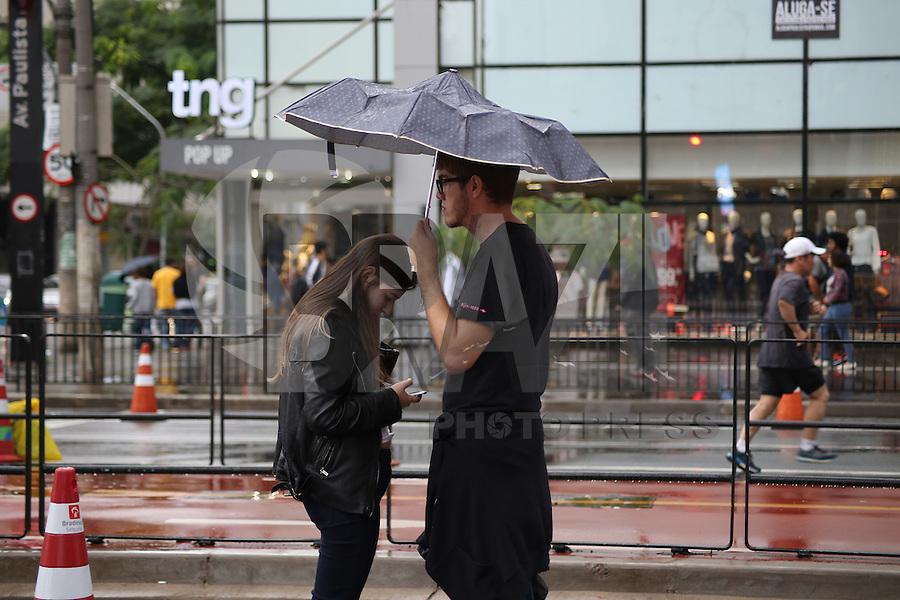 SÃO PAULO, SP, 05.06.2016 - CLIMA-SP - Pedestre se protege da chuva na Av. Paulista, região central de São Paulo (SP), neste domingo (5). (Foto: Yuri Alexandre/Brasil Photo Press)
