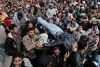 A man passed out and is carried over the crowd at the Ras Jédir border crossing. Tens of thousands of people, mainly Egyptian workers, fled unrest in Libya and crossed the border into Tunisia. Some slept in the open for several days before being processed.  At the same time forces loyal to Col. Gaddafi fought opposition forces in various parts of the country.