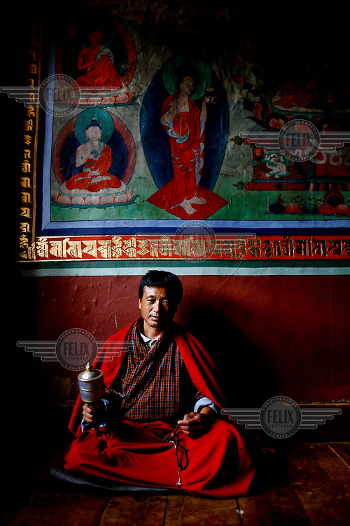 A monk in prayer at the Taktsang (Dzong) Monastery high up in the Paro Valley.