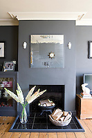 In the living room a square contemporary mirror echoes the simple lines of the black-tiled fireplace below