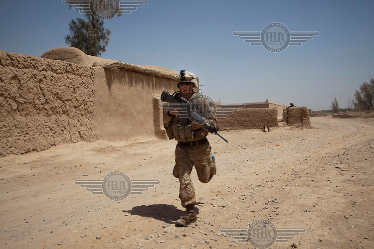 A US marine from 3-6, Lima Company, 2nd Platoon seeks cover in a two hour firefight against the Taliban who attacked the platoon close to their base in northern Marja.
