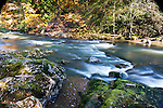Blurred river rapids with moss coverd rocks and Fall colors