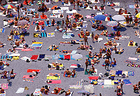 Sunbathers and swimmers crowd a beach in Positano, Italy