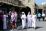 QATAR, Doha, Bazar Souq Waqif , western tourist with arab headgear souvenir and qatari men in traditional white bedouin clothes / KATAR, Doha, Basar Souk Wakif