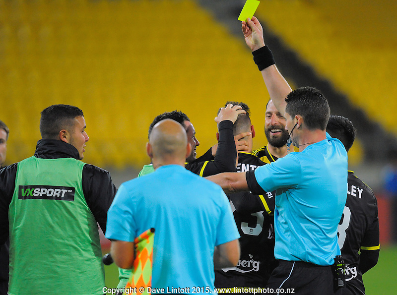Referee Ben Williams brandishes a yellow card as the Phoenix celebrate Matthew Ridenton's goal during the A-League football match between Wellington Phoenix and Adelaide United at Westpac Stadium, Wellington, New Zealand on Friday, 13 November 2015. Photo: Dave Lintott / lintottphoto.co.nz