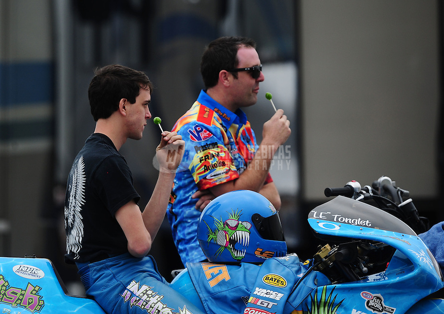 Mar. 10, 2012; Gainesville, FL, USA; NHRA pro stock motorcycle rider L.E. Tonglet (left) eats a lollipop alongside brother G.T. Tonglet during qualifying for the Gatornationals at Auto Plus Raceway at Gainesville. Mandatory Credit: Mark J. Rebilas-