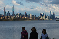 WEST NEW YORK, NJ - APRIL 21: People pass walk as the New York skyline is seen on the background on April 21, 2020 as seen from West New York, New Jersey. (Photo by Kena Betancur/ VIEWpress via Getty Images)