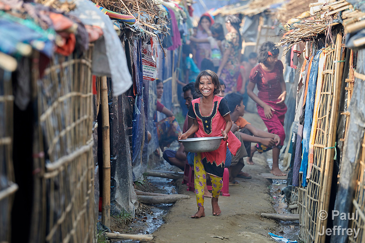 A Rohingya girl walks between makeshift shelters in the Jamtoli Refugee Camp near Cox's Bazar, Bangladesh. More than 600,000 Rohingya have fled government-sanctioned violence in Myanmar for safety in Bangladesh.