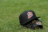 Batavia Muckdogs batting practice hat and TPX Pro glove sit in the grass during practice on June 10, 2014 at Dwyer Stadium in Batavia, New York.  (Mike Janes/Four Seam Images)