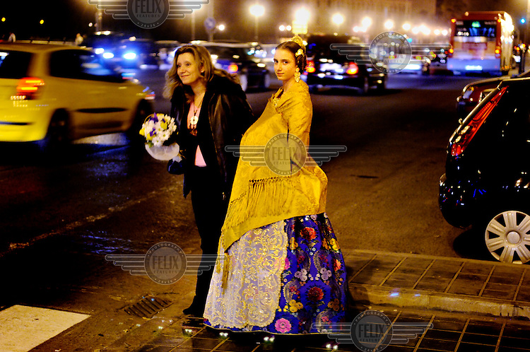 A young woman in traditional costume, accompanied by her mother, waits to cross a busy road on their way to an event.